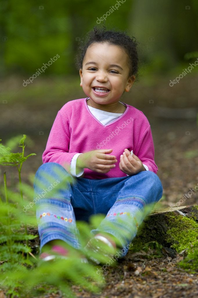 A beautiful mixed race girl sitting on a treestump, laughing and playing with a daisy  — Stock Photo #6802483