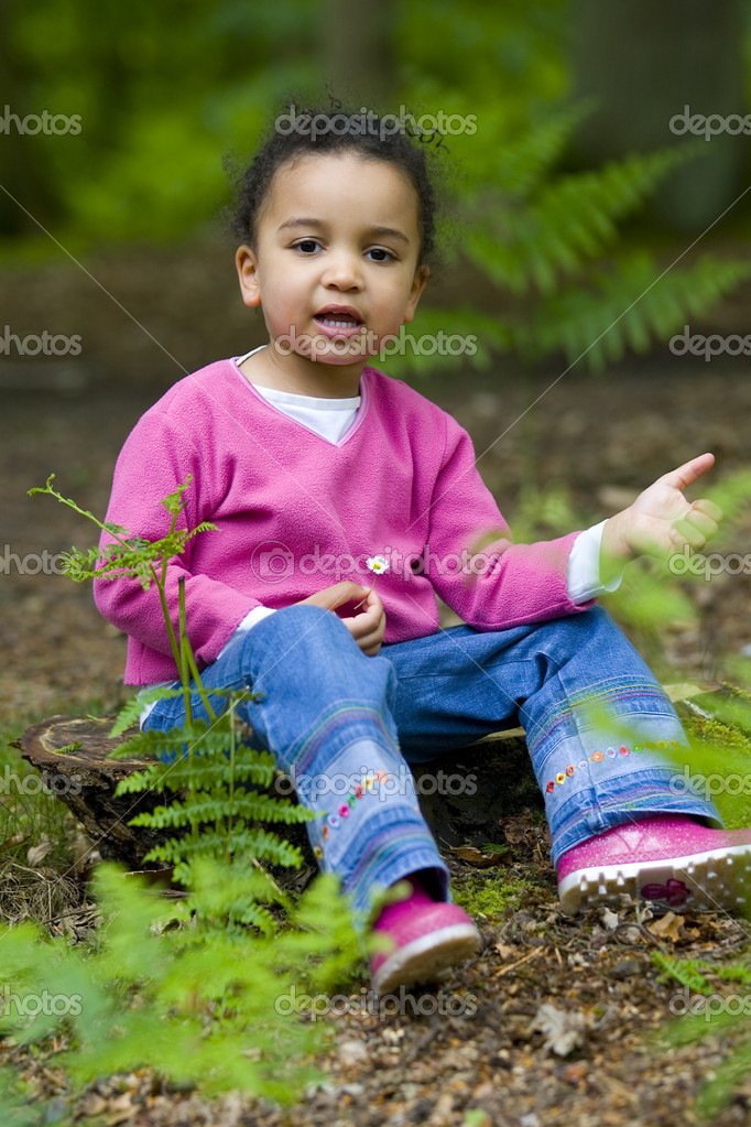 A beautiful mixed race girl sitting on a treestump holding a daisy — Stock Photo #6802492