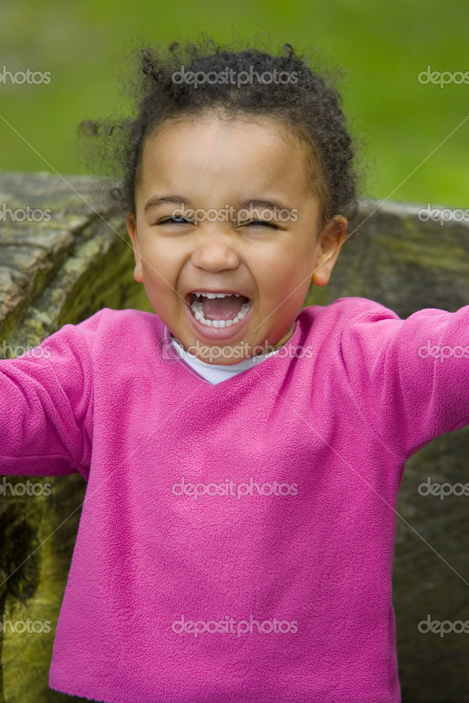 A beautiful mixed race girl sitting on a log and laughing - very loudly  Stock Photo #6802517