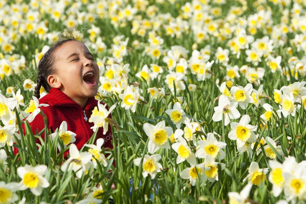 A beautiful young mixed race girl playing in a field of daffodils — Stock Photo #6802559