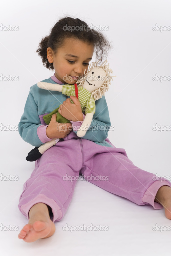 A beautiful mixed race girl playing with her favorite doll  Stock Photo #6802849