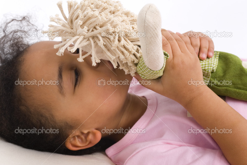 A beautiful little mixed race girl lying in bed and kissing her favorite doll — Stock Photo #6802854