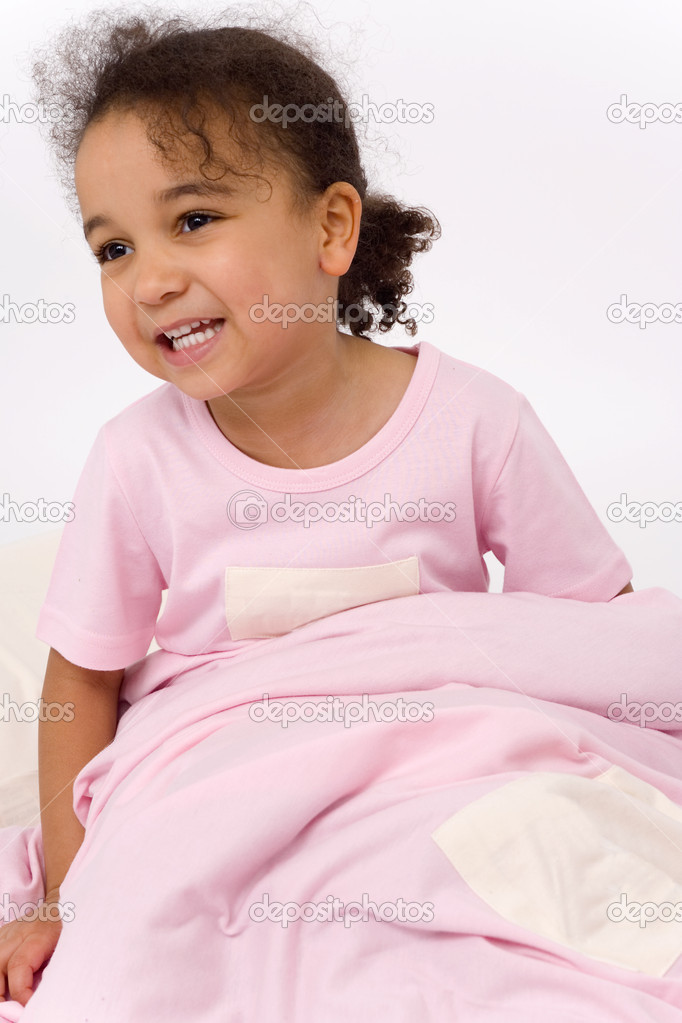 A beautiful little mixed race girl dressed in pink pajamas, sitting up in bed and smiling — Stock Photo #6802855