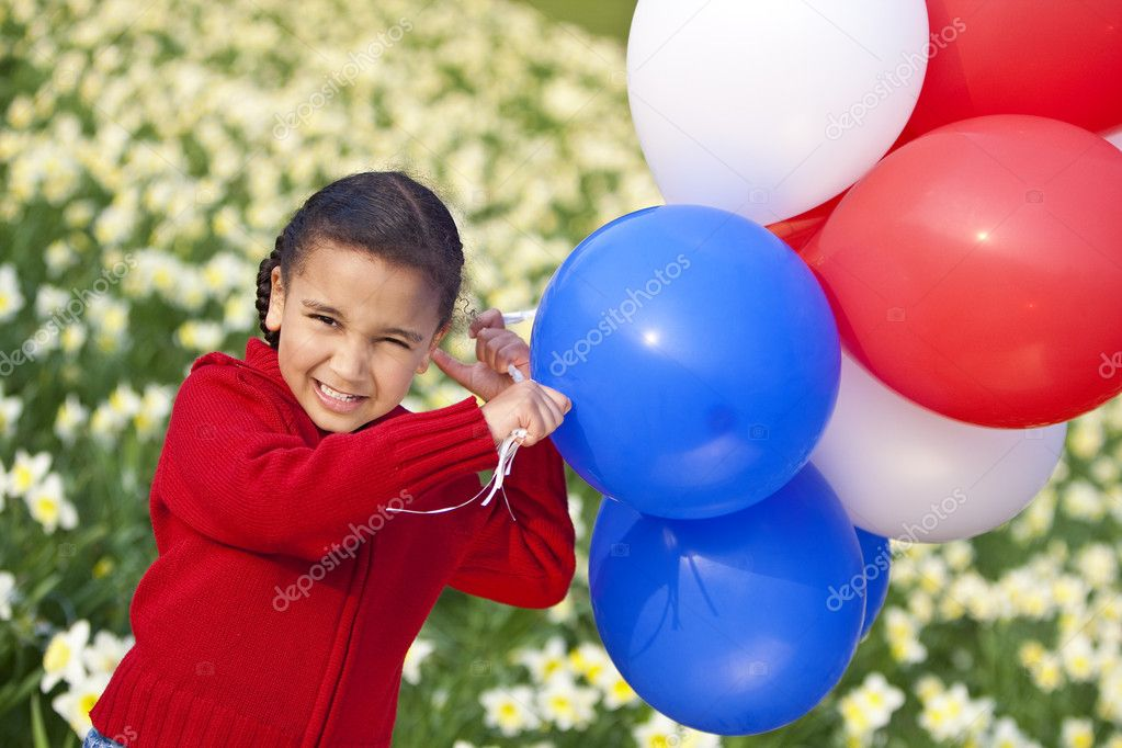 A beautiful young mixed race girl playing with balloons in a field of daffodils — Stock Photo #6802862