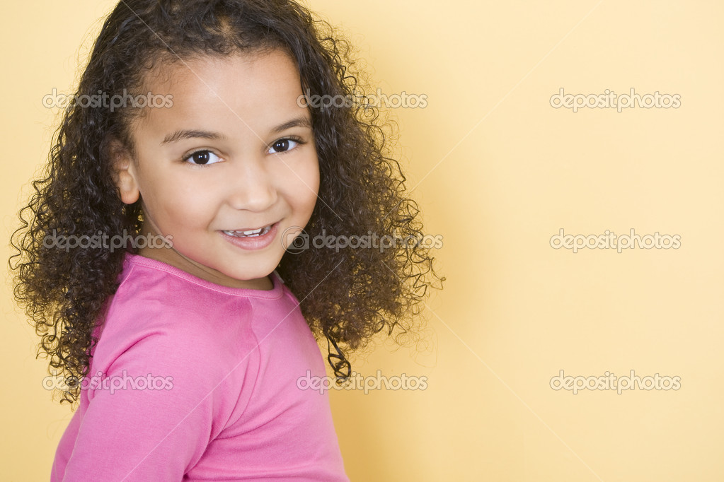 Studio shot of a beautiful young mixed race girl smiling and looking back over her shoulder — Stock Photo #6802902