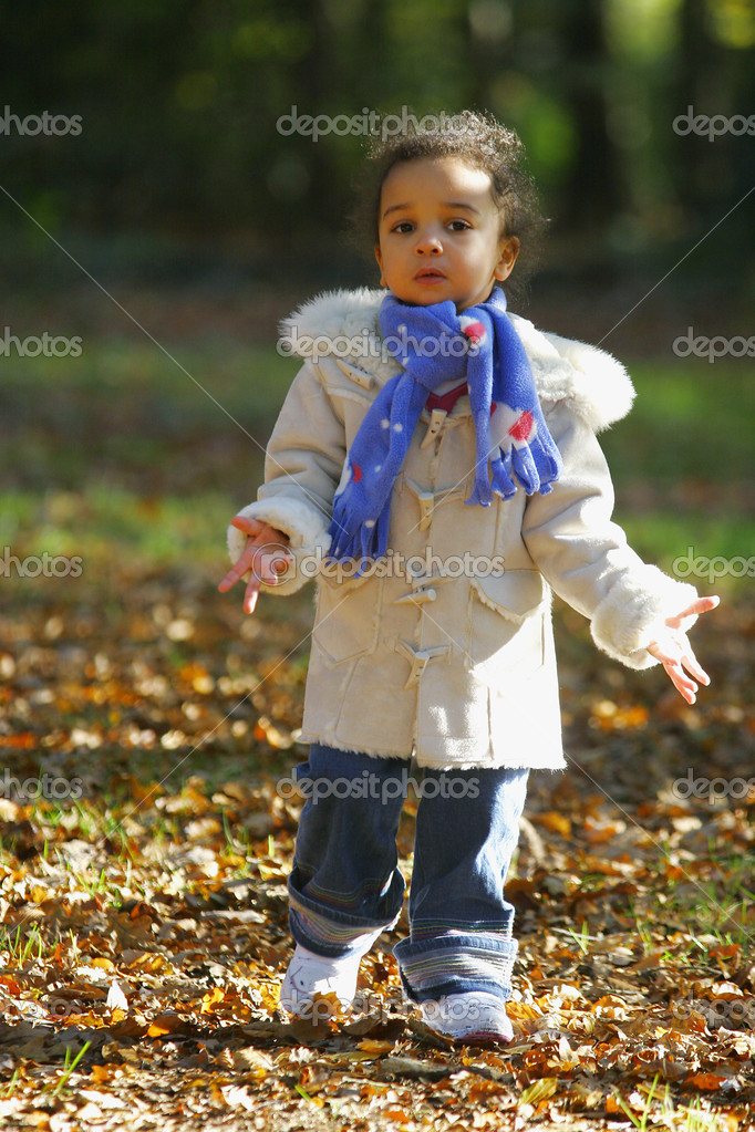 A young mixed race girl in a leaf filled forest — Stock Photo #6802925