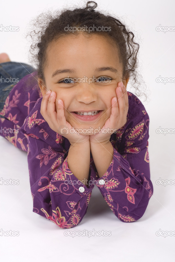 Studio shot of a beautiful mixed race little girl resting on her hands and smiling sweetly for the camera — Stock Photo #6803043