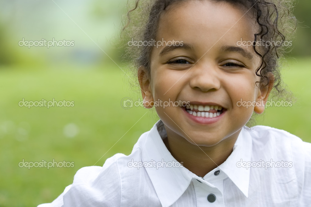 A beautiful mixed race little girl smiles sweetly for the camera — Stock Photo #6803054