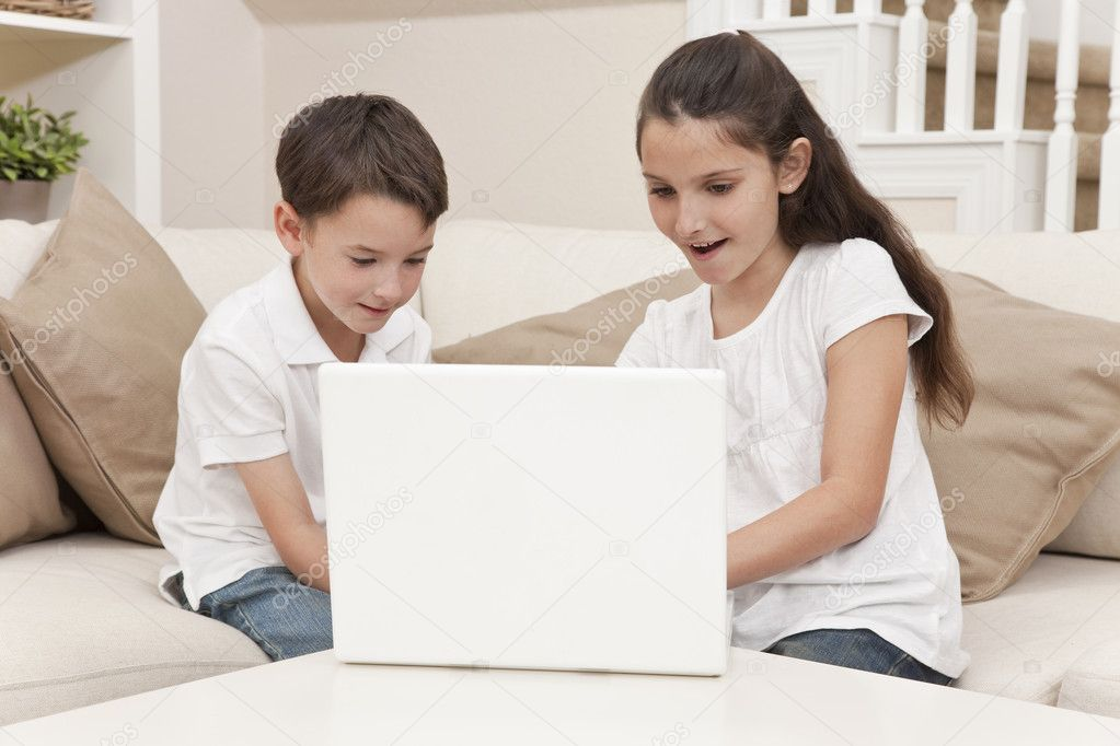 Young boy & girl children using laptop computer on a sofa at home — Stock Photo #6803377