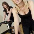 Two Beautiful Young Women On Exercise Bikes At The Gym — Stock Photo