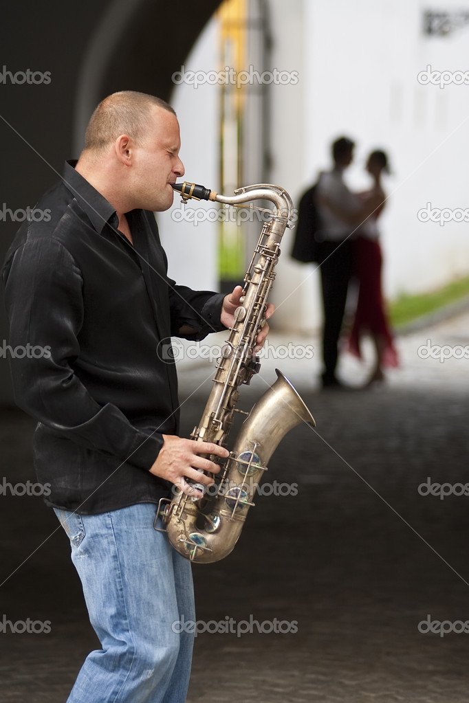 A street musician playing his saxophone serenades two young lovers  Stock Photo #6875303