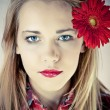 Portrait of young beautiful woman with red flower in her hair — Stock Photo