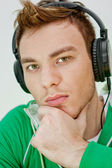 Portrait of a happy young man listen music with headphones — Stock Photo