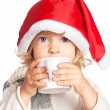 Child in Santa hat drinking hot chocolate — Stock Photo
