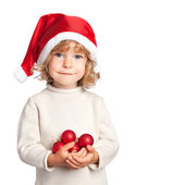 Smiling child in Santa hat with Christmas balls on white backgro — Stock Photo