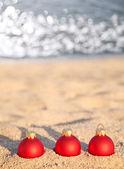 海海岸の 3 つの赤いクリスマス ボール — ストック写真