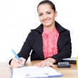 Beautiful young business woman writing on clipboard on her desk — Stock Photo