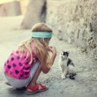 Blonde little girl plays with kitten in street — Stock Photo