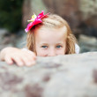 Beautiful blonde little girl girl hides behind a stone — Stock Photo