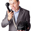 An angry businessman screaming in telephone receiver isolated on — Stock Photo