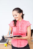 Young happy smiling businesswoman taking notes at the office — Stock Photo