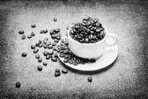 Cup with coffee beans on fabric texture background — Stock Photo