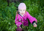Little girl in cap collects flowers — Stock Photo