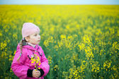 Little girl in field of yellow flowers — Zdjęcie stockowe