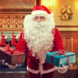 Santa Claus with gifts in decorated living room — ストック写真