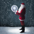 Santa Claus holding glowing planet earth under falling snow — Stock fotografie
