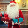 Santa Claus with gifts in decorated living room — Stock Photo