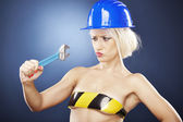 Attractive girl with construction helmet and adjustable wrench. — Stock Photo