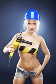 Blonde model with a power drill in jeans shorts. — Stock Photo