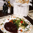 Elegant restaurant plate with a big steak and gravy garnished wi - Photo
