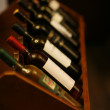 Wine bottles stacked on wooden racks shot with limited depth of — Stock Photo