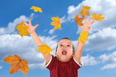 Happy boy reaching for the falling autumn leaves — Stock Photo