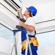 Worker mounting air conditioning unit - Stock Photo