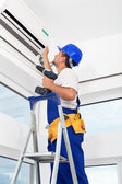 Worker mounting air conditioning unit — Stock Photo