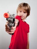 Boy with gun toy — Stock Photo