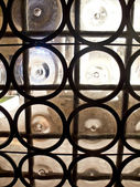 An old stile iron window made with the bottom parts of bottles, — 图库照片