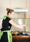 Young woman cooks dinner in the kitchen — Stok fotoğraf