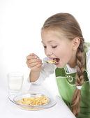 Tjej äter flingor med mjölk — Stockfoto