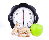 Dietetic loaves with green apple and watches at 6 o'clock — Stock Photo