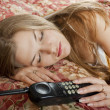 Beautiful woman lying in the bedroom with telephone — ストック写真