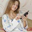Beautiful woman lying in the bedroom with telephone — Stock Photo