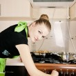 Foto de Stock  : Young woman cooks dinner in the kitchen