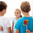 Boys with lollipops and a little girl — Stock Photo