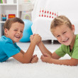 Happy boys laughing and arm wrestling — Stock Photo