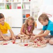 Three kids playing with wooden blocks — Foto de Stock