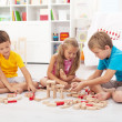 Three kids playing with wooden blocks — Stock Photo